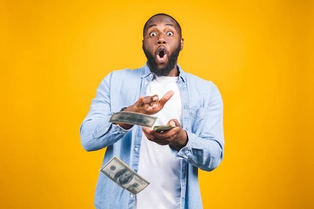 Porträt eines glücklichen jungen afroamerikanischen mannes, der geldbanknoten herauswirft