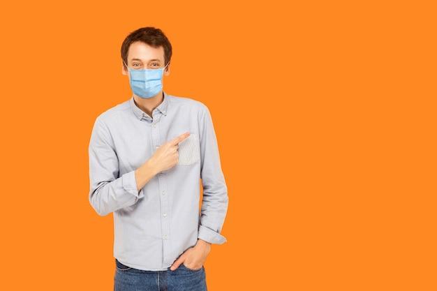 Porträt eines glücklichen jungen arbeitermannes mit chirurgischer medizinischer maske, der steht, zeigt und den leeren kopienraum des hintergrundes zeigt und lächelt. indoor-studioaufnahme auf orangem hintergrund isoliert.