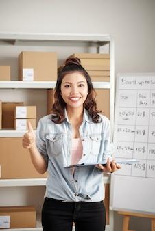 Porträt eines glücklichen jungen asiatischen postangestellten mit lockigem haar, der ordner mit dokumenten hält und daumen nach oben zeigt