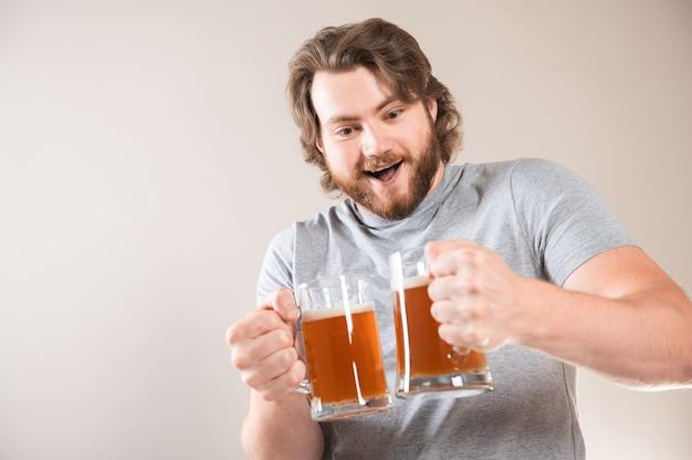 Porträt eines glücklichen jungen bärtigen mannes, der zwei bierkrüge über hellgrauem hintergrund isoliert hält