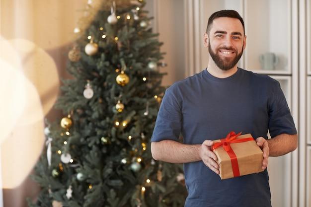 Porträt eines glücklichen jungen bärtigen mannes im t-shirt, der zu hause mit geschenk gegen den weihnachtsbaum steht