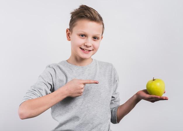 Porträt eines glücklichen jungen, der in der hand seinen finger in richtung zum ganzen grünen apfel zeigt