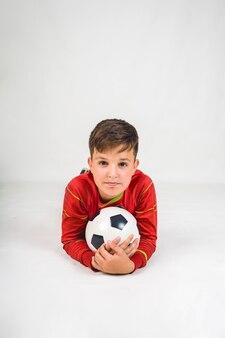 Porträt eines glücklichen jungen fußballspielers in einer roten uniform, der mit einem fußball auf einem weißen hintergrund mit einem platz für text liegt