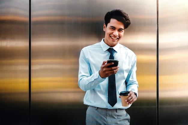 Porträt eines glücklichen jungen geschäftsmannes, der handy in der stadt benutzt. lebensstil der modernen menschen. vorderansicht. an der wand mit kaffeetasse stehen
