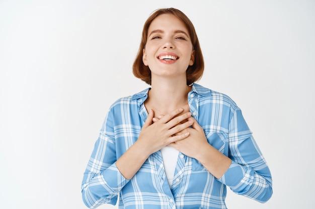 Porträt eines glücklichen jungen mädchens, das die hände auf dem herzen hält, dankbar lächelt, danke sagt, dankbarkeit und freundliche haltung ausdrückt, weiße wand
