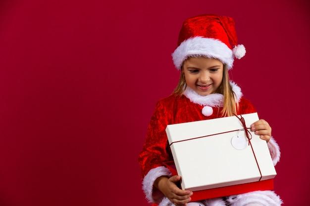 Porträt eines glücklichen jungen mädchens mit einer offenen geschenkbox lokalisiert über roter wand, gekleidet in santa