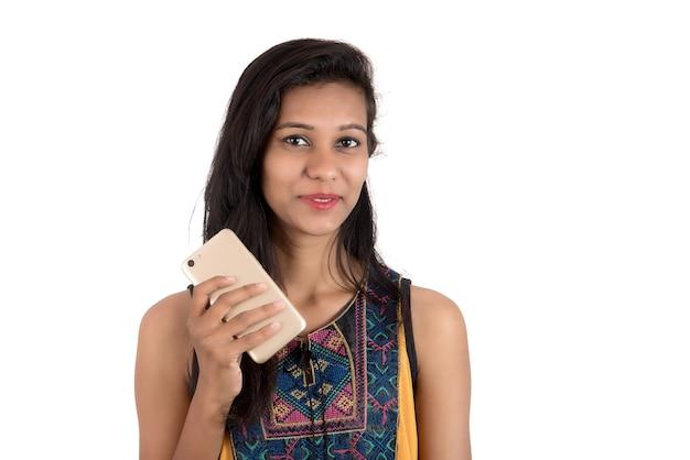 Porträt eines glücklichen jungen mädchens unter verwendung des mobiltelefons lokalisiert über weiß