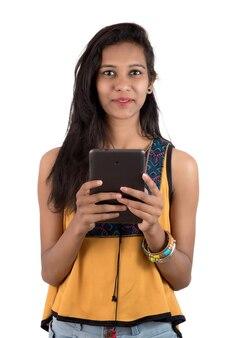 Porträt eines glücklichen jungen mädchens unter verwendung des mobiltelefons lokalisiert über weißer wand
