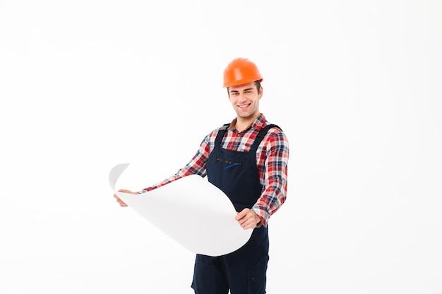 Porträt eines glücklichen jungen männlichen erbauers, der papierentwurf hält