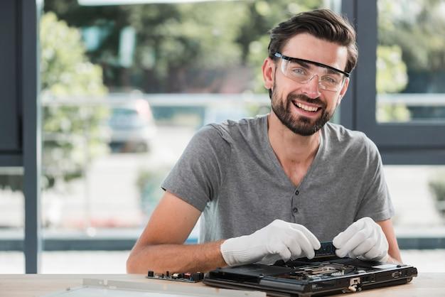 Porträt eines glücklichen jungen männlichen technikers, der computer repariert