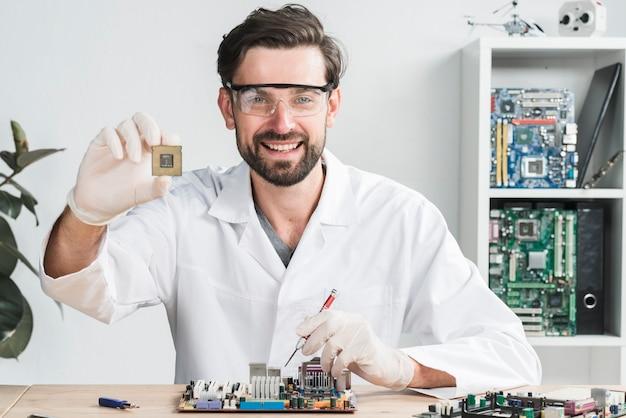 Porträt eines glücklichen jungen männlichen technikers, der computerchip hält