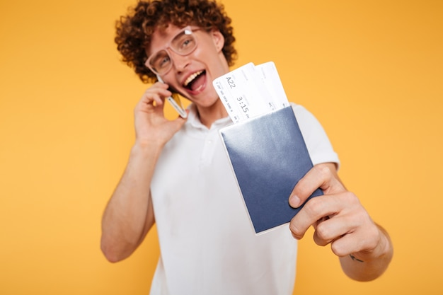 Porträt eines glücklichen jungen mannes, der auf handy spricht