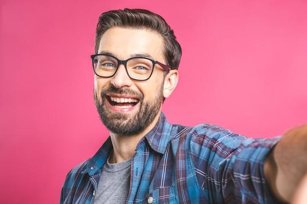 Porträt eines glücklichen jungen mannes, der ein selfie-foto macht
