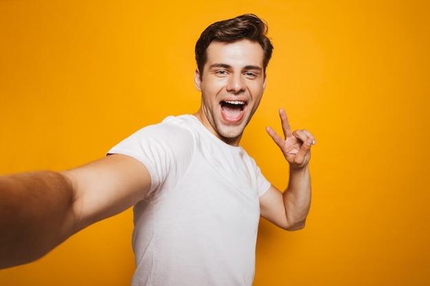 Porträt eines glücklichen jungen mannes, der ein selfie nimmt