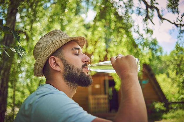 Porträt eines glücklichen jungen mannes, der etwas wasser aus einer flasche trinkt, während er in einem park sitzt und sich ausruht