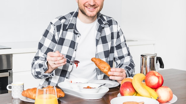 Porträt eines glücklichen jungen mannes, der hörnchen im frühstück isst