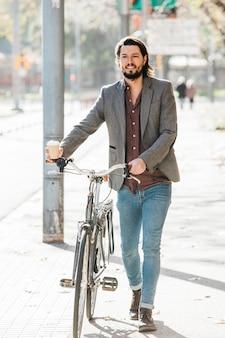 Porträt eines glücklichen jungen mannes, der mit fahrrad auf stadtstraße geht