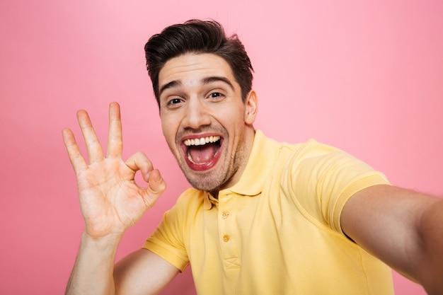 Porträt eines glücklichen jungen mannes, der ok geste zeigt