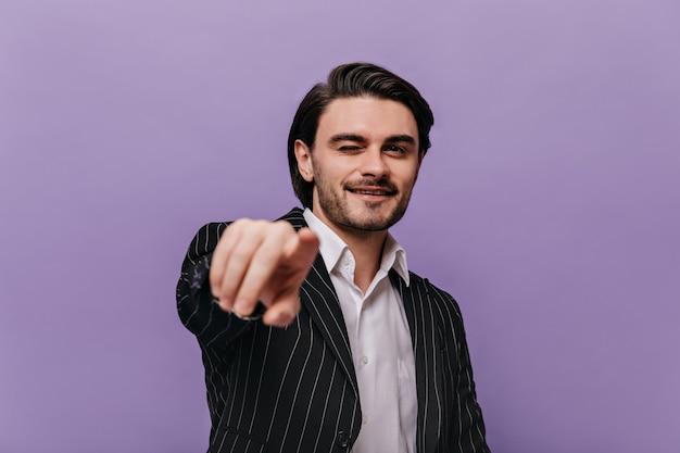 Porträt eines glücklichen jungen mannes in weißem hemd, schwarzer anzug, der gerade aussieht, während er auf die kamera zeigt