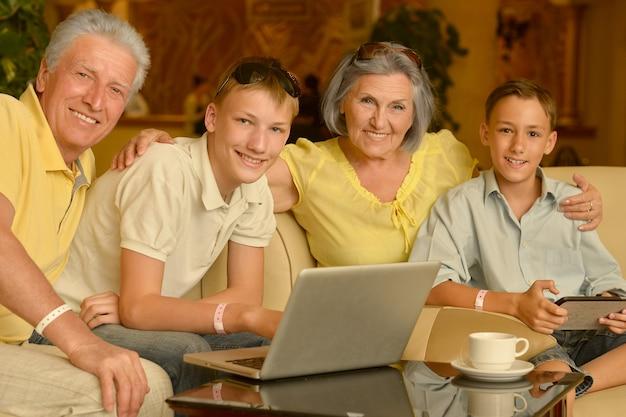 Porträt eines glücklichen jungen mit großeltern und laptop