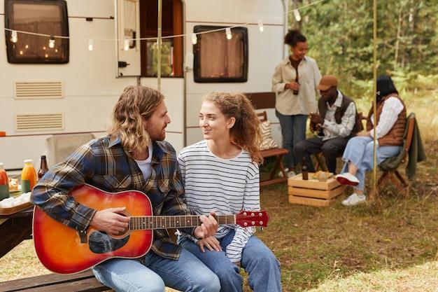 Porträt eines glücklichen jungen paares, das gitarre spielt, während es im freien mit wohnwagenkopie zeltet...