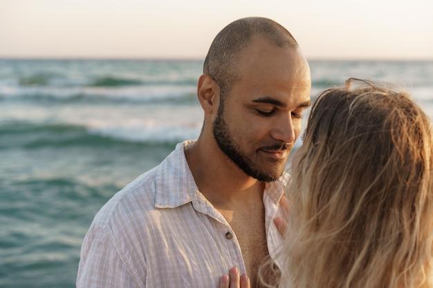 Porträt eines glücklichen jungen paares, das sich am strand umarmt