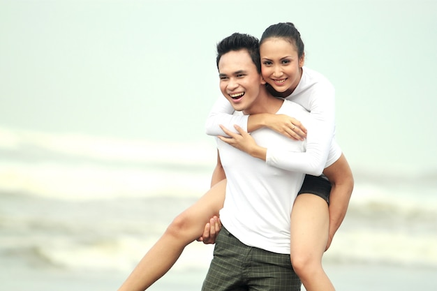 Porträt eines glücklichen jungen paares, das spaß am strand hat
