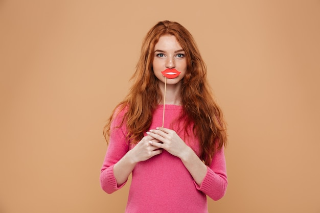 Porträt eines glücklichen jungen rothaarigemädchens, das papierlippen hält