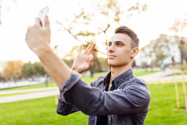 Porträt eines glücklichen kerls, in der sonnenbrille, im park mit einem smartphone stehend.