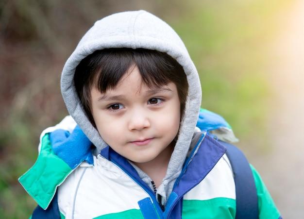 Porträt eines glücklichen kindes, das den warmen stoff draußen spielt im winter trägt