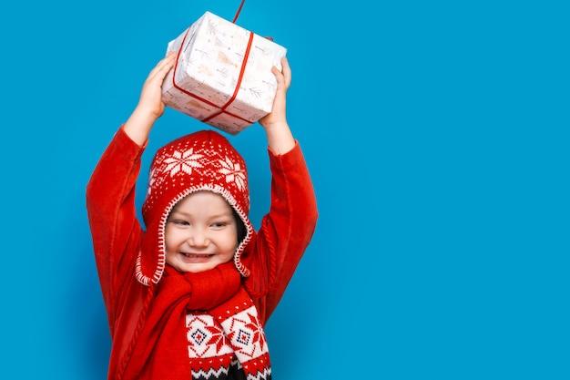 Porträt eines glücklichen kleinen jungen, der ein neues weihnachtsgeschenk hält