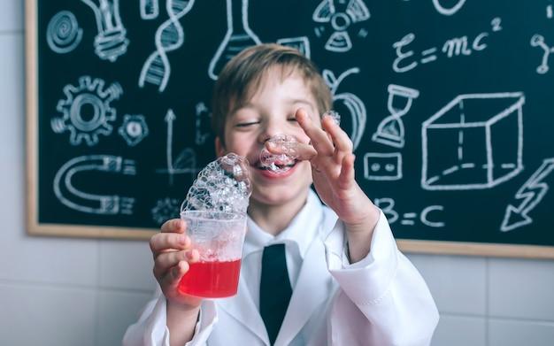 Porträt eines glücklichen kleinen jungen, der glas mit seifenschaum gegen eine tafel mit zeichnungen hält