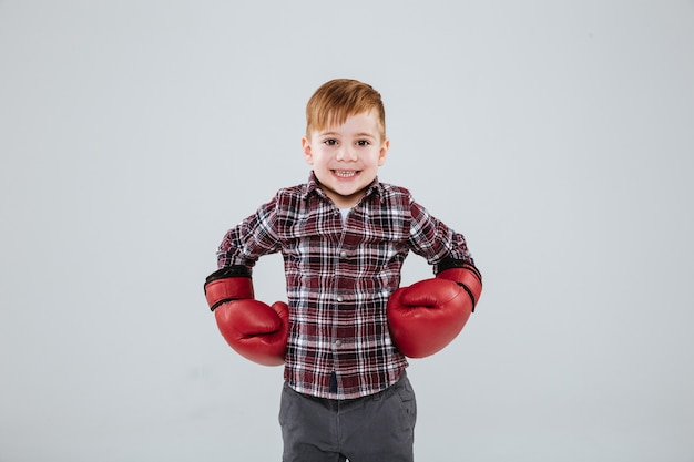 Porträt eines glücklichen kleinen jungen in kariertem hemd und roten boxhandschuhen über weißer wand