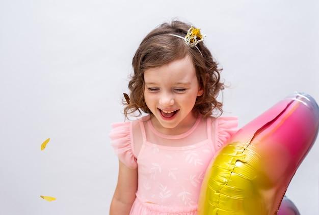 Porträt eines glücklichen kleinen mädchens auf einem weißen festlichen hintergrund mit einem platz für text