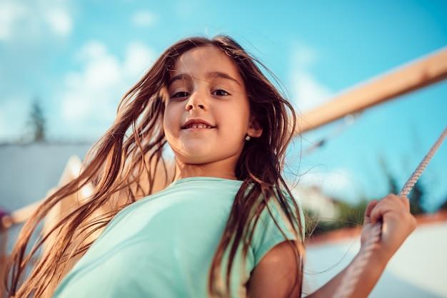 Porträt eines glücklichen kleinen mädchens auf einer schaukel