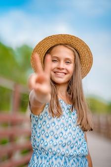 Porträt eines glücklichen kleinen mädchens, das der kamera zwei finger zeigt