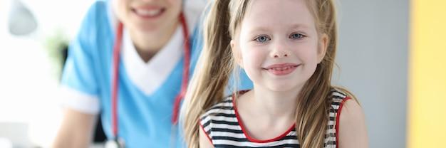 Porträt eines glücklichen kleinen mädchens, das nach guter beratung mit dem kinderarzt beim betrachten der kamera posiert