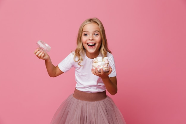 Porträt eines glücklichen kleinen mädchens, das offenes glas marshmallow hält