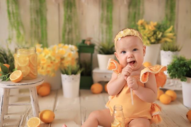 Porträt eines glücklichen kleinen mädchens, des babys, das zitronen isst und limonade trinkt