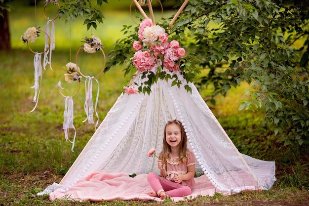 Porträt eines glücklichen kleinen mädchens im sommer in einem park mit blumenwigwam.