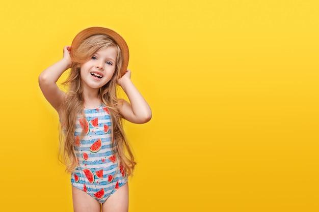 Porträt eines glücklichen kleinen mädchens mit langen haaren in einem badeanzug und einem hut