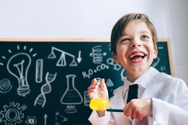 Porträt eines glücklichen kleinen wissenschaftlers, der lacht, während er eine gelbe flüssigkeit in einer flasche mit einem marker zeigt