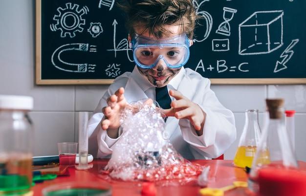 Porträt eines glücklichen kleinen wissenschaftlers mit brille und schmutzigem gesicht, der seine arme hinter glas mit seifenschaum öffnet