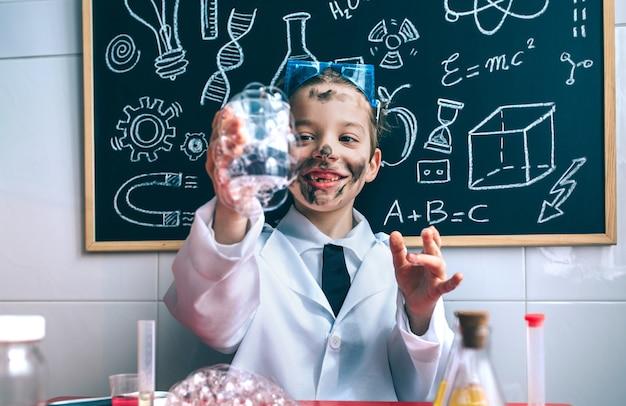 Porträt eines glücklichen kleinen wissenschaftlers mit schmutzigem gesicht, das glas mit seifenschaum gegen eine tafel mit zeichnungen hält