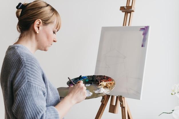 Porträt eines glücklichen künstlers mit einer palette in den händen auf dem vordergrund