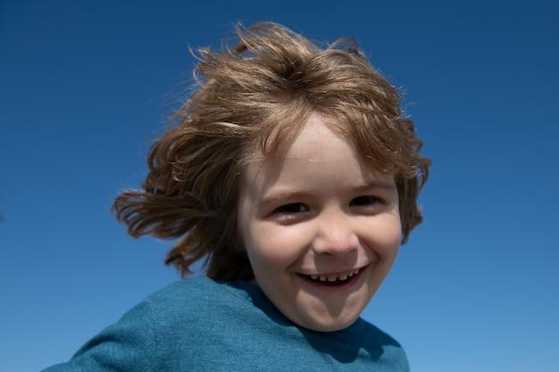 Porträt eines glücklichen lachenden kindes am blauen himmel mit kopienraum. schließen sie das positive kindergesicht.
