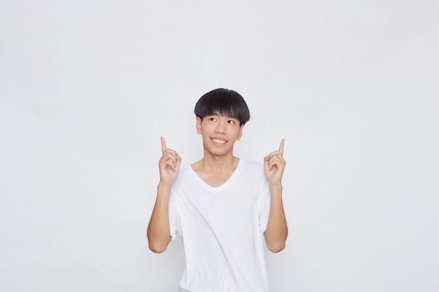 Porträt eines glücklichen lächelnden asiatischen mannes, der lässiges weißes t-shirt trägt, das hand auf leeren raum neben auf weißem hintergrund zeigt