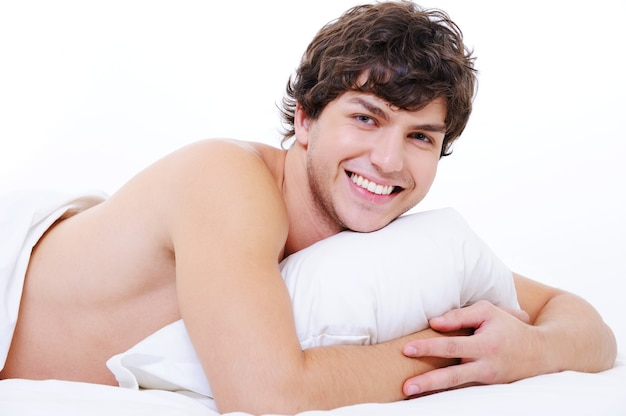 Porträt eines glücklichen lächelnden jungen schönen mannes, der im bett liegt