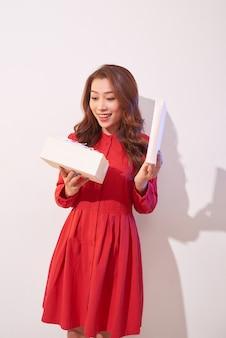 Porträt eines glücklichen lächelnden mädchens, das eine geschenkbox öffnet, die über weißer wand lokalisiert wird