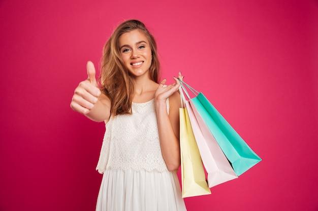 Porträt eines glücklichen lächelnden mädchens, das einkaufstaschen hält